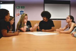 Young adult carers sit in discussion around a large round table