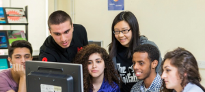 A group of smiling young people of different ethnic backgrounds sit and stand around a computer monitor