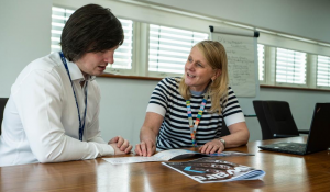 A young man in white shirt sits at a desk alongside a woman in a black and white striped top giving him advice